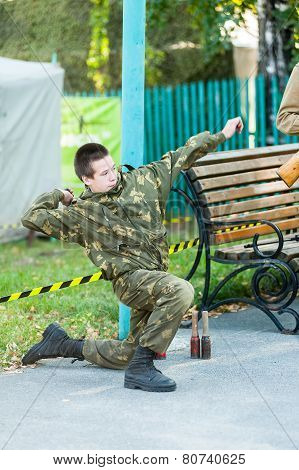 Boy throws hand grenade