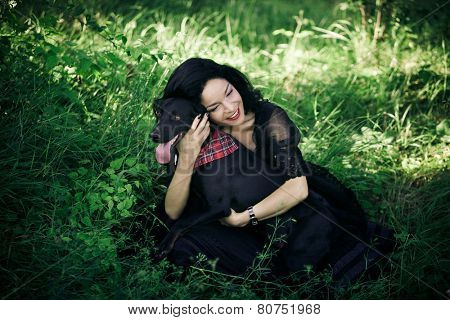 beautiful young woman in black elegant dress sit on grass field with her dog summer day