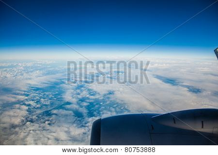 Blue Sky And Engine. View From Airplane Flying In Clouds.