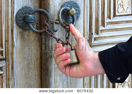 Hand Holding Old Iron Security Lock Of Ornamental Wooden Door