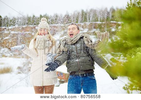 Ecstatic dates having fun in winter forest