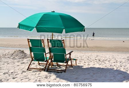 Green sun chairs and umbrella