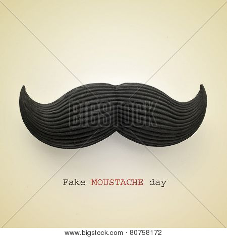 the text fake moustache day and a mustache on a beige background with a retro effect