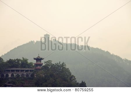 Chinese Pagoda On A Green Hill And Silhouette Of Another Pagoda On A Higher Hill On The Background