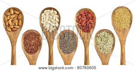 superfood abstract - isolated wooden spoons with almonds, red quinoa grain, pumpkin seeds, chia seeds, goji berry, hemp seed hearts, and golden flax seed