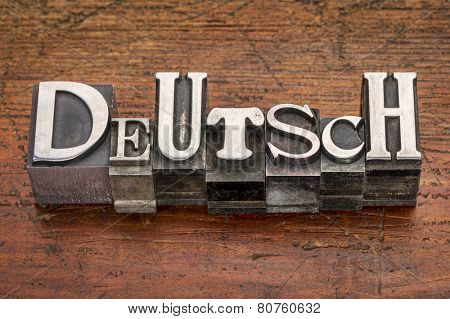 Deutsch (German) word in mixed vintage metal type printing blocks over grunge wood