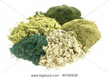 a pile of five healthy green dietary supplement powders (spirulina, chlorella, wheatgrass, kelp and moringa leaf)