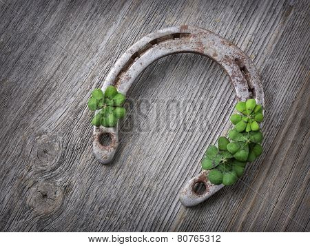 Old rusty horseshoe and four leaf clover on a wooden background