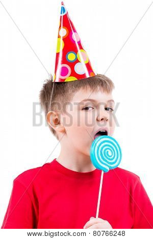 Young boy in red t-shirt and party hat eating colored candy - isolated on white.