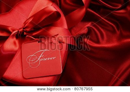 Closeup of chocolate box with gift card on satin background