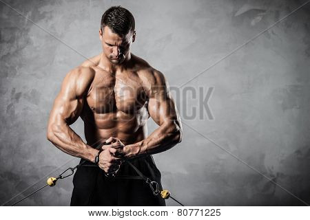 Brutal athletic man pumping up muscles on crossover