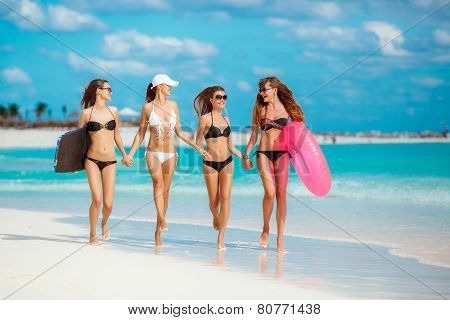 Four slender woman in a bikini with a lifeline near the ocean.