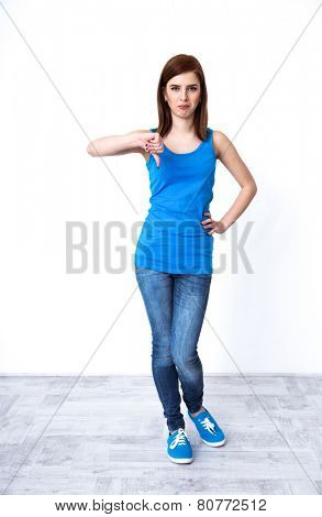 Full length portrait of a beautiful woman gesturing thumbs down