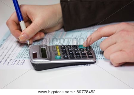 Filling Income Tax Forms With Calculator And Pen