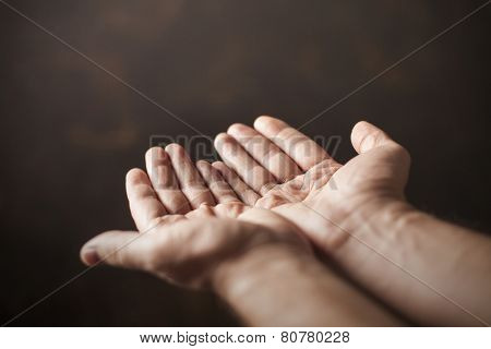 hands begging on a brown background