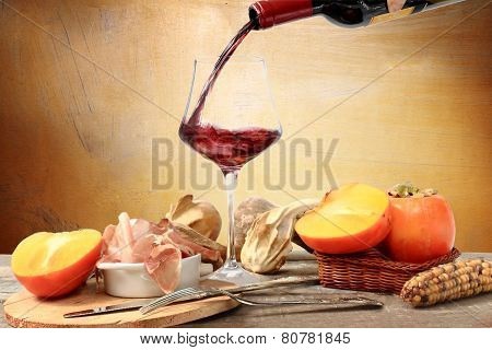 Pouring Red Wine With Over Table Decorated With Winter Food, Persimmon, Cob And Parma Ham