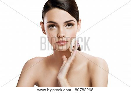 Young woman applying powdered foundation on her face with cosmetic sponge puff, skin care concept