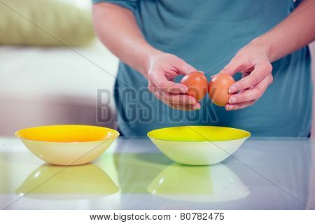 Female hands separating yolk and white of a cracked egg