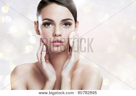 Young woman applying blusher on her face with powder puff, skin care concept