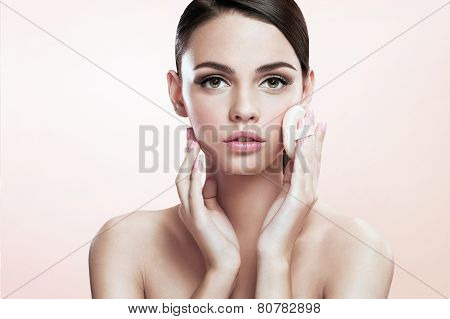 Young lady applying powdered foundation on her face with cosmetic sponge puff, skin care concept