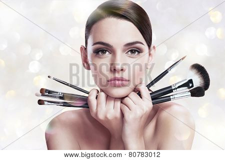 Young beautiful woman with makeup brushes near her face, skin care concept