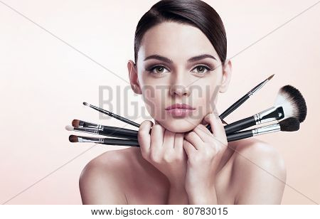 Young beautiful teen girl with makeup brushes near her face, skin care concept