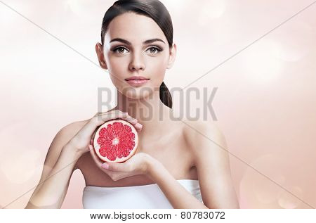 Young woman with grapefruit cut in half, healthy life concept