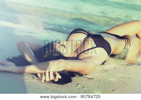 Sexy woman in beach vacation lying in sand in the waves, filtered pic