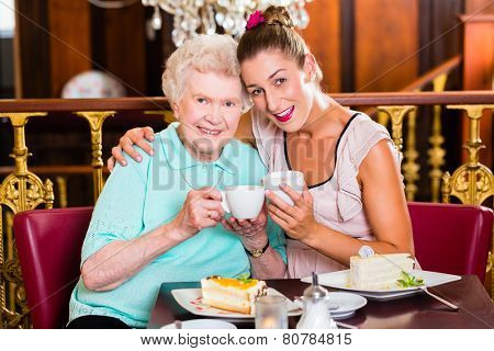 Senior woman and granddaughter drinking coffee and eating cake in cafe