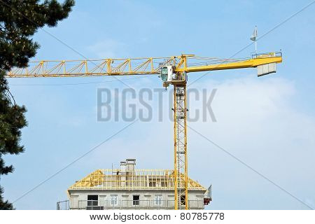 House under construction and yellow crane, roof under construction