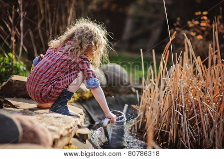 child girl in plaid dress gathering water from pond in spring sunny garden