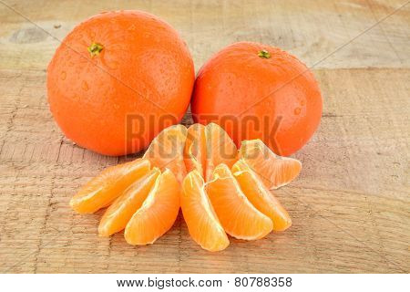 Mandarines With Pieces Isolated On Wooden Table