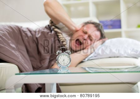 Angry man screaming while his alarm clock ringing