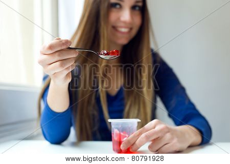 Young Beautiful Woman Eating gelatin At Home.