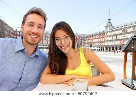 Madrid tourists taking selfie picture at cafe drinking coffee having fun on Plaza Mayor. Portrait of tourist couple sightseeing visiting tourism landmarks and attractions in Spain. Young woman and man