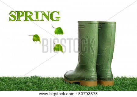 Dirty wellington boots with water droplets on artificial grass