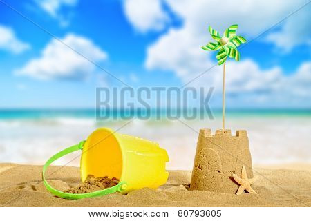Sandcastle on the beach with pinwheel