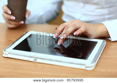 Close up hands woman using tablet in cafe