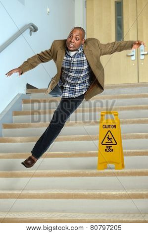 African American businessman falling on stairs with yellow warning sign on steps