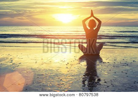 Silhouette of yoga woman meditating on the ocean beach. Fitness. Healthy lifestyle.