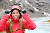 pic of rain  - Laughing happy woman hiking with backpack in rain on trek living healthy active lifestyle - JPG