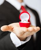 stock photo of propose  - man making proposal with wedding ring in red gift box - JPG