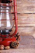 stock photo of kerosene lamp  - Kerosene lamp with cones ans walnuts on wooden planks background - JPG
