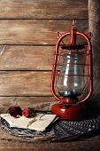 picture of kerosene lamp  - Kerosene lamp with dried rose and letter on wicker mat and wooden planks background - JPG