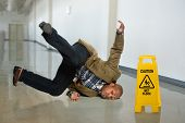 picture of precaution  - African American businessman falling on wet floor in office - JPG