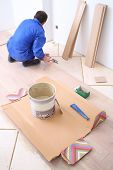 foto of floor covering  - Man puts laminate flooring in white room - JPG