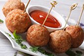 stock photo of meatballs  - Fried meatballs on skewers and tomato sauce on a plate close-up horizontal ** Note: Shallow depth of field - JPG