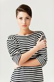 foto of young woman posing the camera  - Fashionable young short hair woman in striped clothing keeping arms crossed and looking at camera - JPG