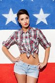 stock photo of young woman posing the camera  - Fashionable young short hair woman posing against American flag background - JPG