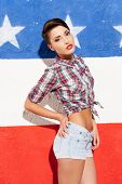stock photo of young woman posing the camera  - Beautiful young short hair woman posing against American flag background and looking at camera - JPG